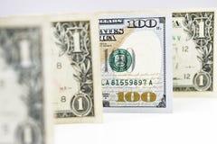 Makroen sköt av en ny 100 dollarräkning och en dollar Arkivfoto