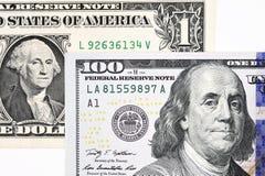 Makroen sköt av en ny 100 dollarräkning och en dollar Arkivfoton