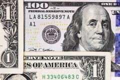 Makroen sköt av en ny 100 dollarräkning och en dollar Arkivbild