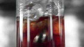 Makrofors av glass mycket med kuber för en is och röda alkoholer som blandar med en bartendercoctailsked glass martini arkivfilmer