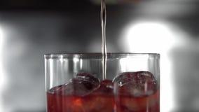 Makrofors av röda martini som häller i ett exponeringsglas som är fullt med kuber för en is Martini påfyllning per exponeringsgla stock video