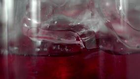 Makrofors av röda martini som häller i ett exponeringsglas som är fullt med kuber för en is Martini påfyllning per exponeringsgla arkivfilmer