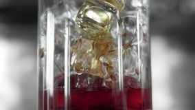 Makrofors av röda martini som häller i ett exponeringsglas som är fullt med kuber för en is Martini påfyllning per exponeringsgla lager videofilmer