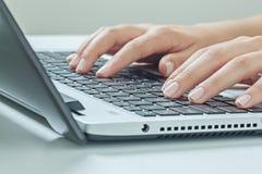 Makrofoto von den weiblichen Händen, die auf Laptop schreiben Geschäftsfrauarbeit Stockbilder