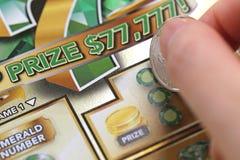 Makrofrau, die Lottoschein am prize Bereich verkratzt Stockfotos