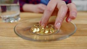 Makrofrauenhand nimmt gelbe Kapsel von der Platte und von der Rückkehr stock footage
