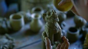 Makrofrauenhandsaubere Lehm-Hundeskulptur mit Schwamm stock footage