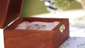Makrogesamtlänge von Eheringen des Weißgolds in der Holzkiste auf dem Tisch Dekorationen für Hochzeitszeremonie im Freien stock footage