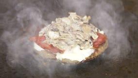 Makrokoch Lays Mushrooms auf gebratenem Fleisch-Stück mit Käse-Schinken stock video footage