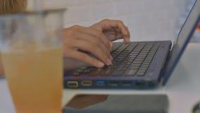 Makromädchen übergibt Text auf Laptop-Saft auf Tabelle stock video footage
