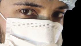 Makronärbild av det mänskliga ögat En man i en medicinskt maskering och lock stock video