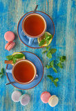 Makron och två kopp te på en blå bakgrund Arkivbilder