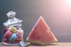 Makron vattenmelon, plommon, apelsinskivor på en trätabell Begreppet av hem- komfort och värme Arkivfoto