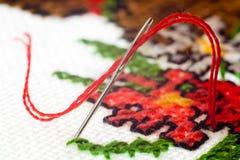 Makronadel mit rotem Faden Stockbild