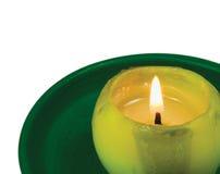 Makronahaufnahme der grünen brennenden Kerze, lokalisierte glühende Flamme Stockfotografie
