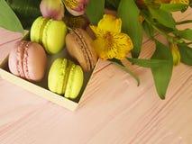 Makrone auf rosa hölzernem, Alstroemeriablume, packen romantisches ein Lizenzfreie Stockbilder