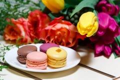 Makronen auf Platte mit Blumenstrauß Lizenzfreie Stockfotografie