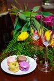 Makronen auf Platte mit Blumenstrauß Stockbilder