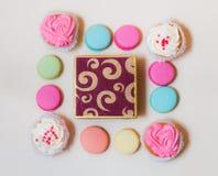 Makronen, kleine Kuchen und Geschenkbox auf beige Hintergrund Lizenzfreies Stockbild