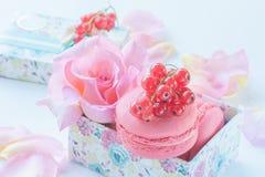 Makronen mit roten Johannisbeeren, Eibische auf dem Hintergrund von schönen Blumen von Rosen in einer Geschenkbox Nachtischnahauf stockbild