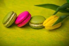 Makronenlebensmittel mit gelbem Hintergrund der Tulpen für Valentinsgrüße bemuttern Frauentag Ostern mit Liebe Lizenzfreie Stockbilder