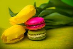 Makronenlebensmittel mit gelbem Hintergrund der Tulpen für Valentinsgrüße bemuttern Frauentag Ostern mit Liebe Lizenzfreies Stockbild