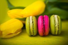 Makronenlebensmittel mit gelbem Hintergrund der Tulpen für Valentinsgrüße bemuttern Frauentag Ostern mit Liebe Stockfotos