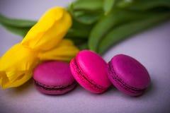 Makronenlebensmittel mit Tulpen zacken violetten Hintergrund für Valentinsgrußmutter-Frauentag Ostern mit Liebe aus Stockfoto