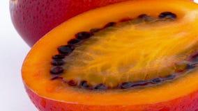 Makroschießen Hälfteschnitt der reifen Tamarillo-Fruchtmasse Langsam, drehend auf die Drehscheibe lokalisiert auf dem Weiß stock video