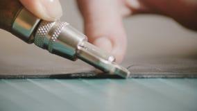 Makroschuß der erstaunlichen Nahaufnahme, Hände, die rauen Rand des schwarzen Stückes Leders auf spezieller Tabelle mit Berufswer stock video