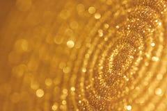 Makroschuß der Platte mit goldenen Scheinen und bokeh Lizenzfreie Stockfotografie