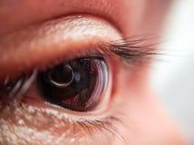 Makroschuß eines Auges und der Reflexion des Kameraobjektivs lizenzfreies stockbild