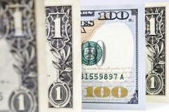 Makroschuß eines neuen 100 Dollarscheins und eines Dollars lizenzfreie abbildung