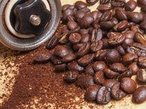 Makroschuß von Kaffeebohnen und von Metallmanuellem Schleifer mit Kaffee Lizenzfreie Stockfotos