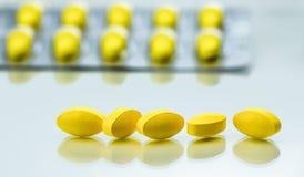 Makroschussdetail von gelben ovalen Tablettenpillen auf weißem Hintergrund mit Blisterpackungshintergrund Stockfoto