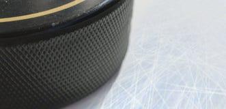Makroskott av den svarta hockeypucken på isisbana Royaltyfri Fotografi