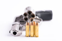 Makroskott av en öppen revolver och kulor Arkivbild