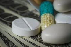 Makroskott av preventivpillerar på en hög av dollar Arkivfoton