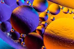 Makroskottet av olja bubblar med vatten på färgrik bakgrund Utformad abstrakt bild för utrymme och för universum planeter Royaltyfri Foto