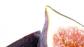 Makroskytte av övredelen av två halvor av frukt för gemensam fikonträd Långsamt rotera på skivtallriken som isoleras på viten arkivfilmer