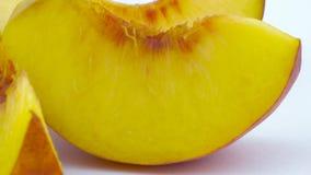 Makroskytte av mogna persikaskivor Långsamt rotera på skivtallriken som isoleras på den vita bakgrunden stock video