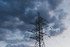 Maktöverföringslinje pol mot mörkt - blå molnig himmel royaltyfri fotografi