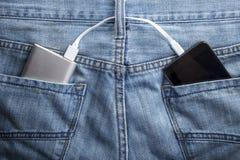Maktbanken ligger i en bakficka av jeans mobiltelefonchargen fotografering för bildbyråer