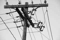 Maktpoler och kraftledningar i svartvitt fotografering för bildbyråer