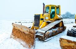 Maktskyffel och bulldozer i snö arkivfoto