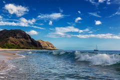 Makua beach view of the wave with beatiful mountains and a sailboat in the background, Oahu island