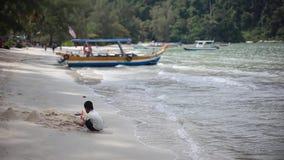 Malásia, Penang, o 22 de dezembro de 2015 Crianças asiáticas que jogam no bote na praia branca da areia 1920x1080 video estoque