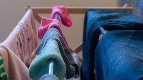Mal adapté, paires de socquettes séchant sur un support de blanchisserie avec les vêtements de la femme comprenant des blues-jean photo libre de droits