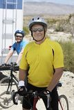 Mal Bicyclist Standing With Woman no fundo Imagens de Stock