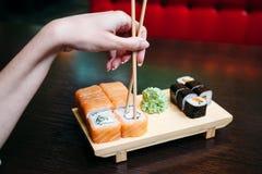 Mal de jeune femme mangeant des sushi avec des baguettes photographie stock
